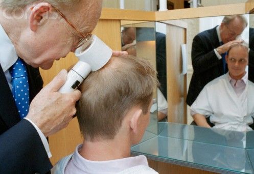 Examining Man for Baldness Treatment