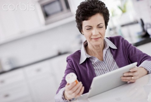 Middle-aged woman using digital tablet to refill prescription