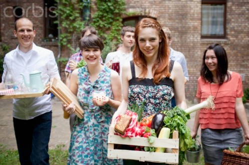 Group of smiling friends carrying food for garden party